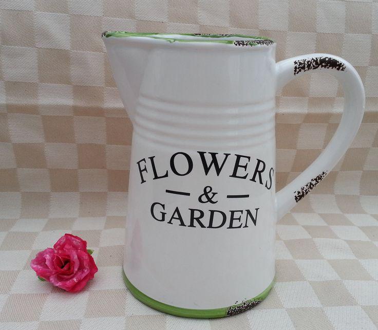 Schenkkan - voor bloemen - 1 liter  Deze schenkkan is speciaal gemaakt voor bloemen, aan één zijde staat de tekst: FLOWERS & GARDEN. De kan van aardewerk is wit van kleur met een groene boven- en onderrand. De bruine plekjes zijn bewust niet geglazuurd, wat een brocante effect geeft! Inhoud: 1 liter.