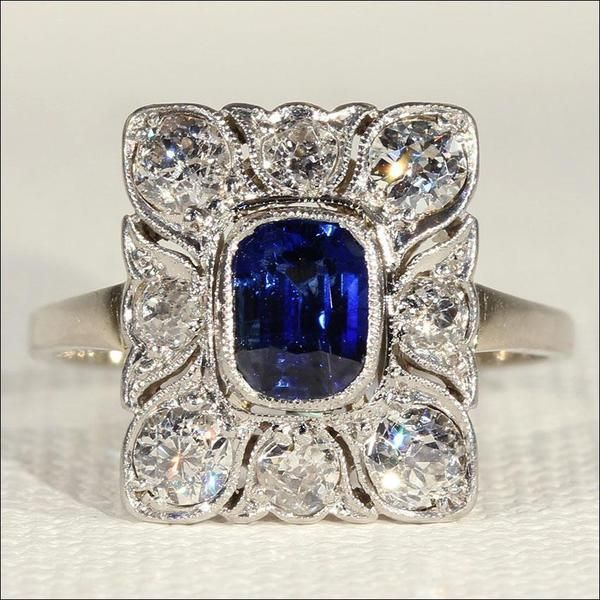 Antique Belle Époque Sapphire and Diamond Engagement Ring in 18k Gold and Platinum. The center stone is an approximately 1 carat sapphire in a rich, deep blue.