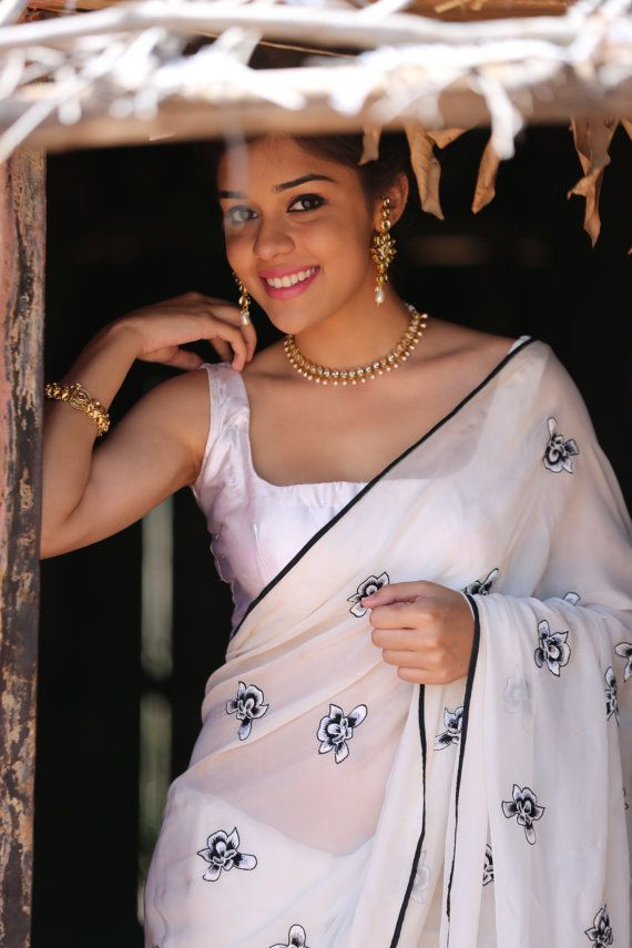 Presenting the royal Iris on a milky white, ethereal pure chiffon saree with pallu adorned with white and black Iris flowers, exquisitely handcrafted with silk shading. Here's a six yards of your statement black-and-white color palette, fresh and welcoming, off the beaten path. Please visit www.eastandgrace.com and subscribe to our newsletter to buy!