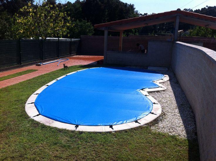 Cobertor de piscina con forma de riñón, confeccionado con un tejido micro- perforado y anclado al suelo mediante tornillería inox escamoteable y sistema de cinchas.
