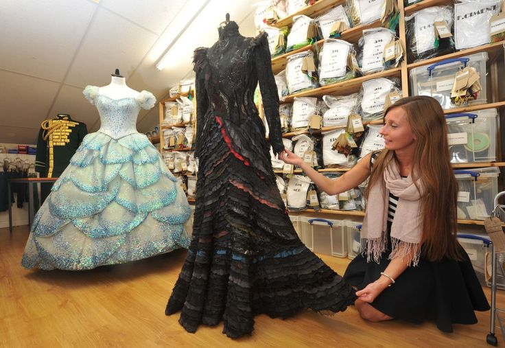 """Assistant costume supervisor Hannah Williams with the dresses belonging to Elphaba and Glinda, behind the scenes at the workshop for the costumes in the theatre production """"Wicked"""" in Stratford-upon-Avon."""