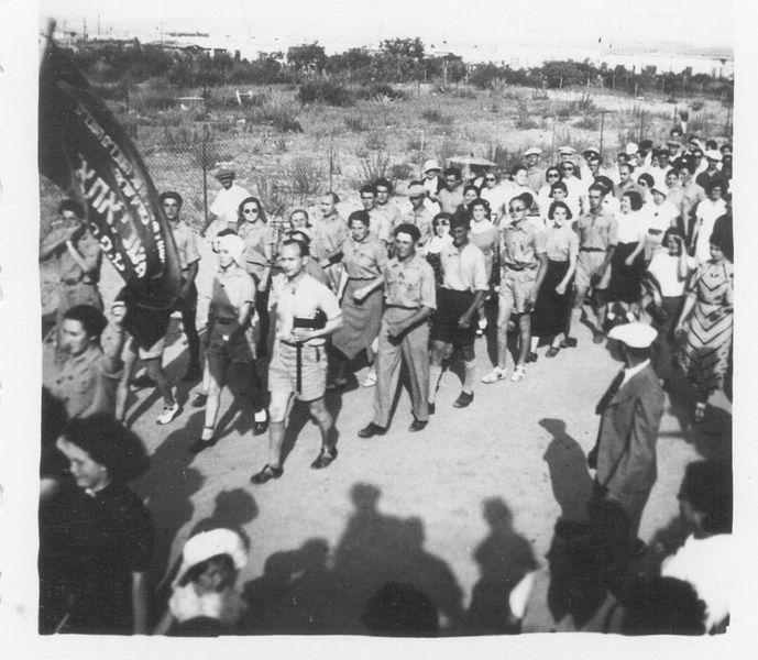 פועלים צועדים בסך ברחוב ומסביבם הקהל המתבונן בהם.שם תורם הצילום: בית-פישר…