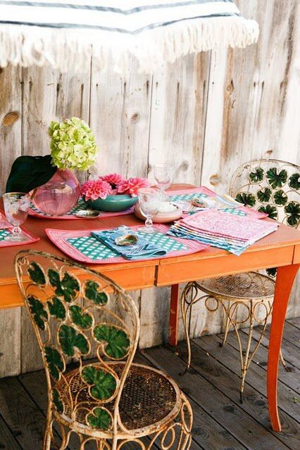 wrought iron garden chairs with green leaf detailorange table and floral composition - Garden Furniture Kerry
