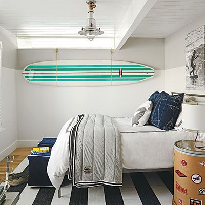 Surfer boy's bedroom! The striped navy rug mixes well with fun surfboard art. Coastalliving.com