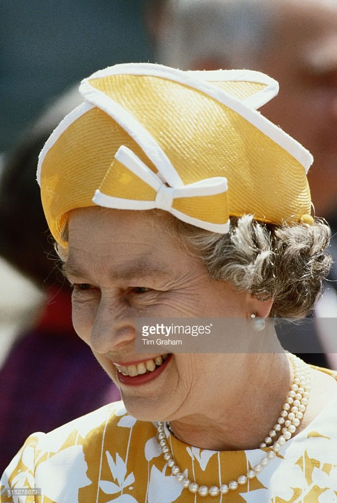 Queen Elizabeth Ii Wearing A Yellow Hat With White Trim