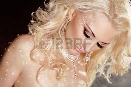 Gros plan de blonde fille mod�le sexy dans les cristaux scintillaient sur la peau avec les cheveux boucl�s et maquillage photo