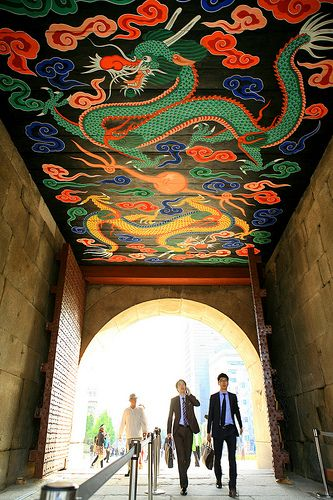 businessmen walk under the #Sungnyemun Gate. As you can see above, a vivid image of a dragon is displayed. | #Seoul | #Korea