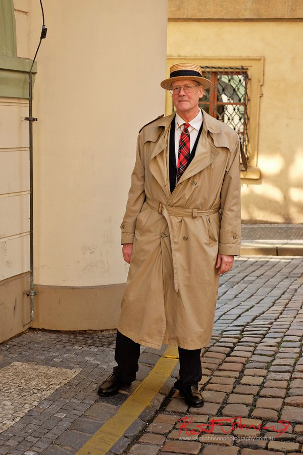 An Ameriacn gentlemen in Prague wearing a suit and trenchcoat with a tartan tie, collar bar and boater hat. Photographed by Kent Johnson for Street Fashion Sydney in Prague.