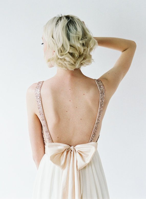 This gown features a plunging neckline, open sides, and a striking back. The skirt is made on the bias using almond chiffon, which flows effortlessly from the waist to the floor. The gown is tied together beautifully with a silk bow that is both elegant and dramatic.</p> <p>The bodice is lined with a stretch satin, and lies close to the skin. …</p>