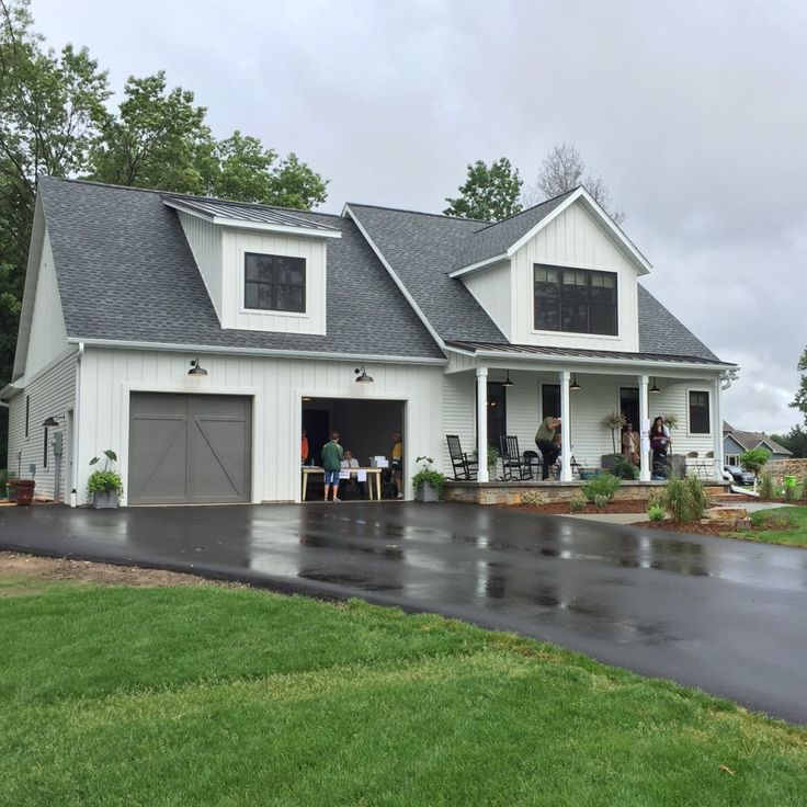 Wisconsin Parade Home is open | Holly Mathis Interiors chelsea gray garage doors SW watery - porch ceiling white vinyl siding black windows - metal outside and painted wood inside