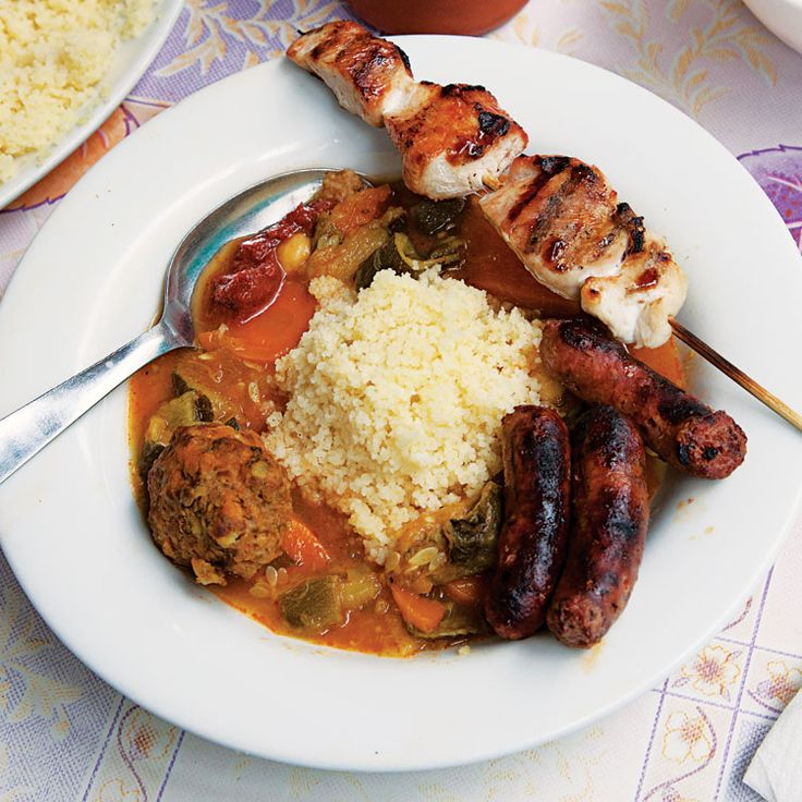 Couscous Royale (Couscous with Grilled Meats)_ A plate of fluffy couscous is lavished with meatballs, lamb chops, chicken skewers, merguez sausage, and a saffron-scented chickpea stew in this celebratory dish, a staple at Moroccan restaurants in Paris. This recipe first appeared in our November 2012 issue along with Jay Cheshes's story Couscous Royale.