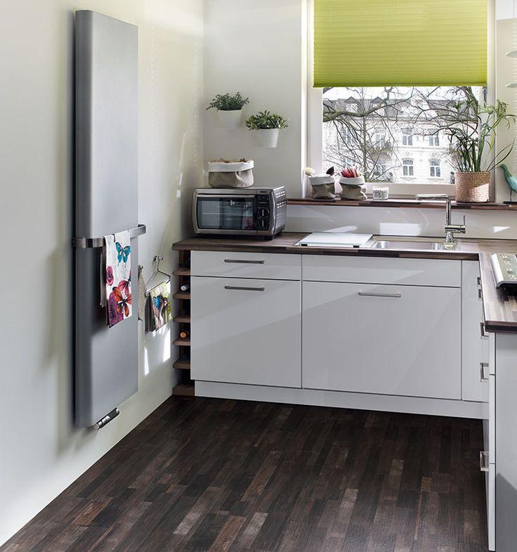 En bra plats för en radiator i köket finns på en smal mellanvägg. Du kan placera en vertikal designradiator på den och utrusta den med en handduksstång att hänga kökshanddukar eller trasor på. Vertikal designradiator Purmo Paros.