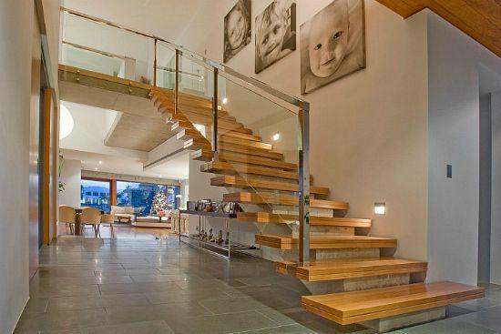 Escada de concreto aparente com degraus de madeira e guarda corpo de inox e vidro. Linda!