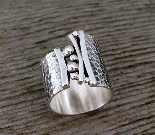 Bridges Ring. A beautiful band of sterling expands across the finger with grace. Captured within the opening a bridge of small granules and graceful lines. Measures 18mm at its widest narrowing to 12mm.