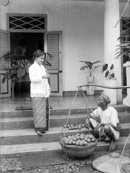 File:COLLECTIE TROPENMUSEUM Een Europese vrouw in sarong en kebaya bekijkt op de stoep van haar huis te Buitenzorg de vruchten van een fruit...