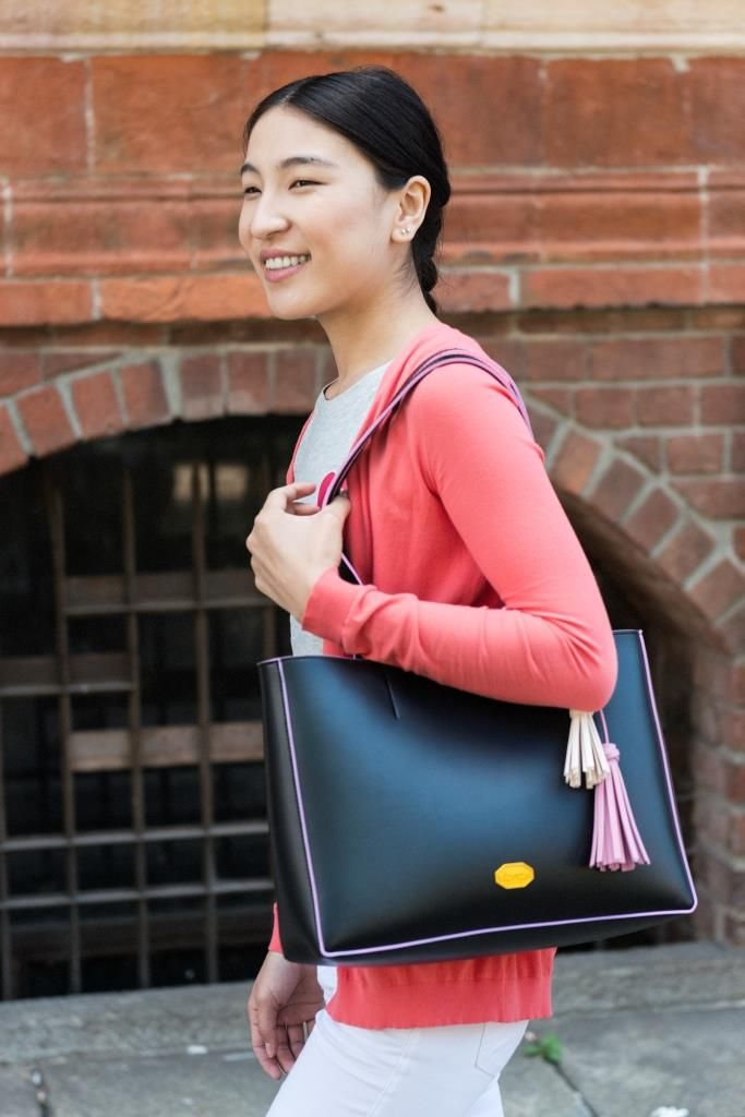 Trendy with quality. Black rubber travel bag with pink finish and beige/pink fringes.