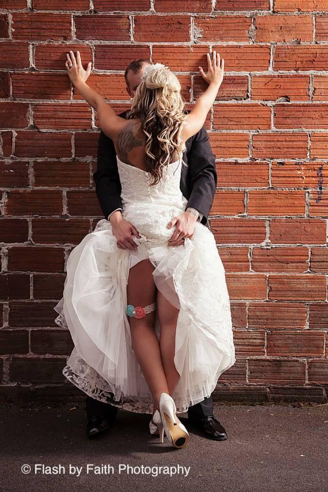 Sexy wedding photo. Brick wall. Garter belt photo.