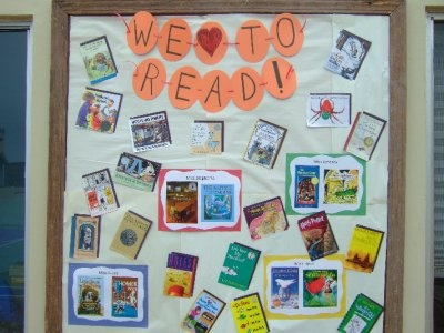 we love to read banner on bulletin board with students in hearts reading a book..