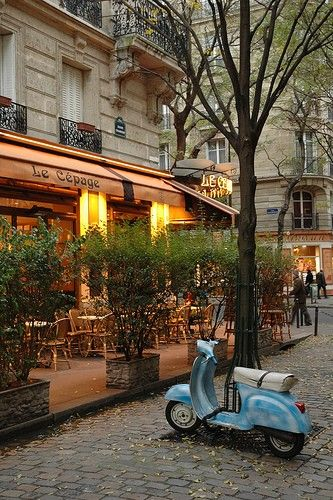 Street Cafe in Paris. This little Vespa Scooter helps to be more mobile. I Love dining Alfresco...
