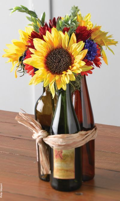 Wine bottles used as 50th birthday party decorations. We love this filled with sunflowers and gerber daisies.