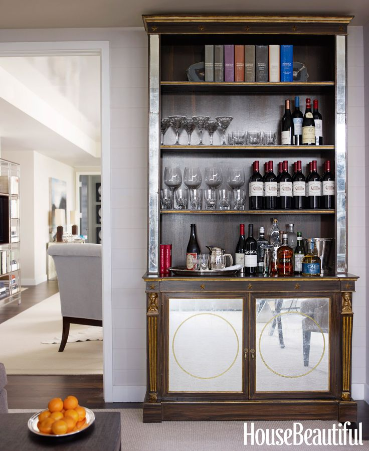 An antique bookcase doubles as a bar in this Manhattan apartment designed by Phoebe and Jim Howard. Glassware by William Yeoward Crystal. - HouseBeautiful.com