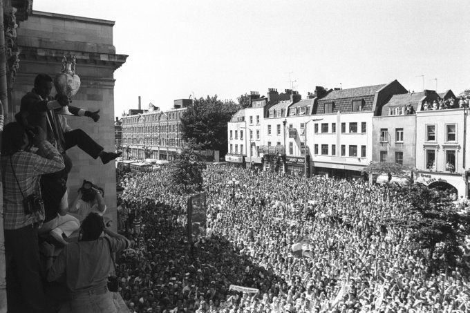 Dated 28th May, 1989: Here we see the late, great David Rocastle dancing (rather precariously) on the balcony of Islington Town Hall, League Championship trophy in hand, as thousands of Arsenal fans pack the streets below during the Gunners' homecoming parade that followed their title-clinching 2-0 victory over Liverpool two days previous…