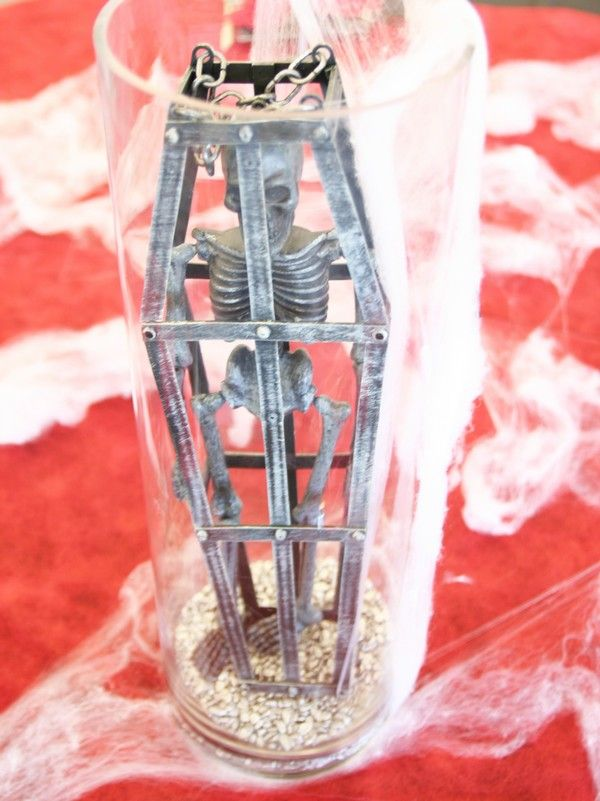Un dernier invité fait son apparition au milieu de la table : un squelette, enfermé dans son cercueil, lui-même placé dans un vase cylindrique ! Depuis combien de temps est-il là ?