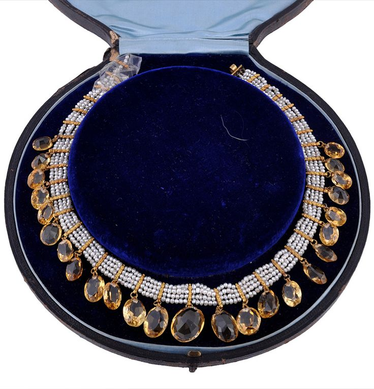 A LATE 19TH CENTURY PEARL, CITRINE AND GOLD MOUNTED FRINGE NECKLACE CIRCA 1870, The four rows of uniform pearls interspaced by granulated gold bars suspending graduated oval cut citrines, in a circular brown leather case with blue velvet interior, Oval cut citrines measuring 19mm to 10mm long, 38cm long