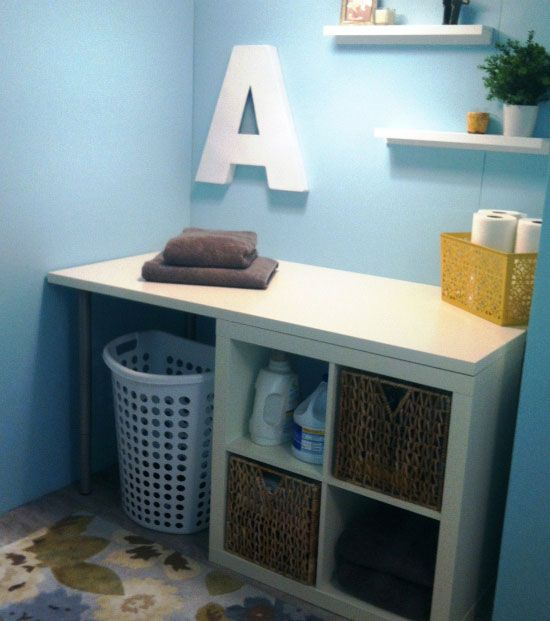 DIY Laundry Storage Table... Just buy a cubby, a tabletop, and some legs to make your own! With a bigger tabletop, this could also be an awesome study desk, crafting table... so many possibilities :)