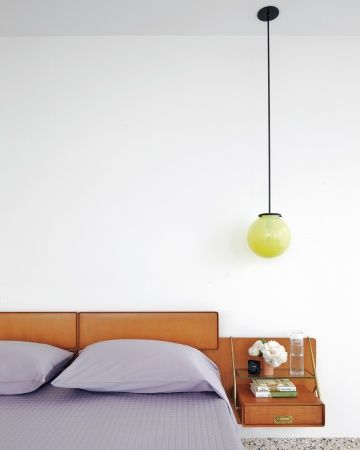 A Bedroom Oasis - the kind of place that makes you want to take a nap. The vintage bed, with its cantilevered nightstands, almost seems as though it's floating. The globe light has a nice glow even when it's off.
