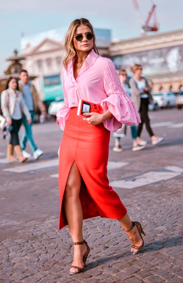 Thassia Naves usa camisa rosa bufante com saia vermelha com fenda e sandália de onça