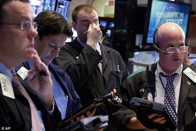 One trader in New York holds his head in disbelief following the the plunging of stock markets around the world during early trading on Monday