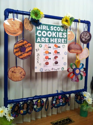 Daisy Girl Scout Cookie Booth.    Painted PVC pipe. Girls decorated flowers at the bottom with their first name & photo.