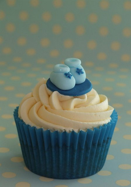 vanilla cupcake for a new arrival with buttercream swirls and decorated with handmade blue fondant baby booties