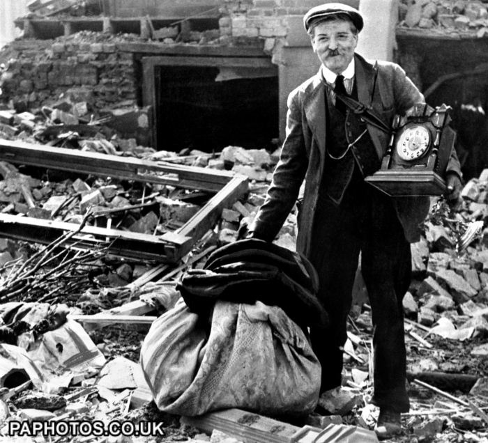 A Londoner, still smiling, while recovering the remains of his belongings from the rubble of his bomb-damaged home.