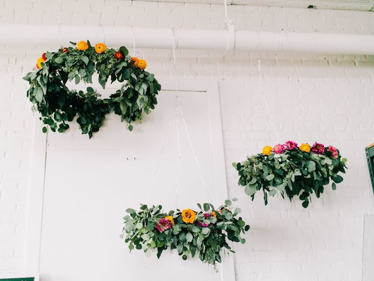 Project by Janie Medley  	Photos by Rachel May Photography  	   	  	   	Decorate your ceiling with hanging floral arrangements! We'll show you how to create your own blooming chandeliers in a few easy steps.   	   	  	   	Ingredients:  	 		Seeded Eucalyptus and Silver Dollar Eucalyptus 	 		Fresh Flowers (I used ranunculus and zinnias) 	 		Scissors 	 		Floral Wire 	 		Green Wire Wreath – I used one large and two small ones   ...