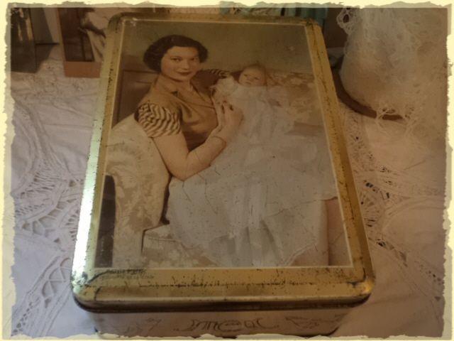Een oude trommel gemerkt vanMelle. met een afbeelding van moeder en baby uit de jaren '50. Bovenop staat Rosario ? ruiter photografie de la coeur. Aan de zijkant van de trommel feestvierende mensen. Volgens eigenaar afbeelding van Luxemburgse prinses met haar kindje. 25,5 cm. lang 18,5 cm breed 9,5 cm hoog.
