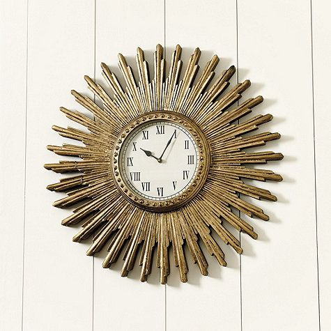 The staggered rays and beaded details of our Clara Sunburst Clock create an instant focal point above a window, mantel or grouped with other art. Hand carved of mango wood and hand finished in aged antique gold. Clara Sunburst Clock features: Glass lensBlack spear handsQuartz movementUses one AA battery (not included)