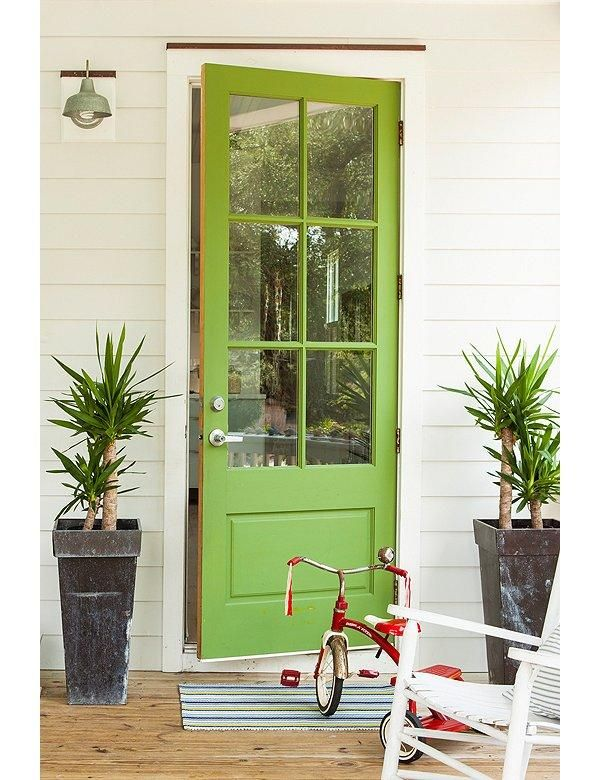 """Modern Whimsy: Airy windowpanes let light flood in and give off a sense of welcoming openness. The retro-cool lime green door, sculptural pots and plants, and striped mat tell visitors this home is fun and kid-friendly but still design conscious. Get more happy and cheerful interior design ideas on """"7 Fabulous Colorful Front Door Ideas"""" on the One Kings Lane Style Guide!"""