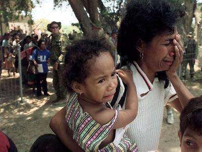 DILI, EAST TIMOR - A woman and her child cry   after they landed at Dili airport, October 8. Some 90 East Timorese   refugees were returned by plane to the territory after having been   taken by Indonesian authorities to West Timor during   pro-Indonesia militia violence.