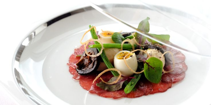 In this carpaccio recipe, lamb is garnished with quail eggs, green beans and pickled walnut. The carpaccio dish is lightly smoked for a dram...