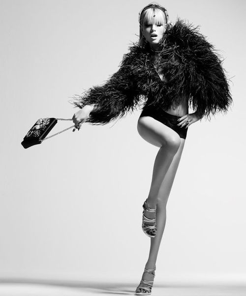 Great fashion shot. Model has movement and lengthening in her pose. Studio shoot, black and white, fashion photography.