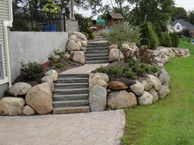 The problematic hill is solved with proper drainage away from the home and a set of steps to a patio. The home is terraced using natural stone with plantings on either side of the walk with a natural stone retaining wall to the lawn.