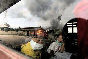 Children wear masks while studying in a classroom in Karo district as Mount Sinabung continues to spew out volcanic ash