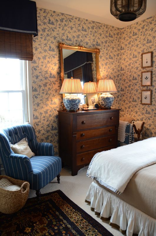 Blue and white bedroom, chest of drawers, two vase lamps, mirror, blue chair, two quilt rack in the corner, rug.