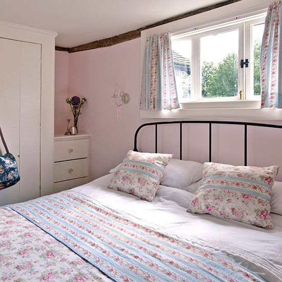 Pink bedroom with pink walls, floral stripe curtains and bedlinen