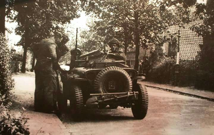 """Recce Jeep, Oosterbeek,  September 1944.Lance-Sergeant Bill Bentall of """"D"""" Troop, 1st Airborne Reconnaissance Squadron, with Dutch civilians on the Bakkerstraat in Oosterbeek. Copyright: D van Woerkom."""