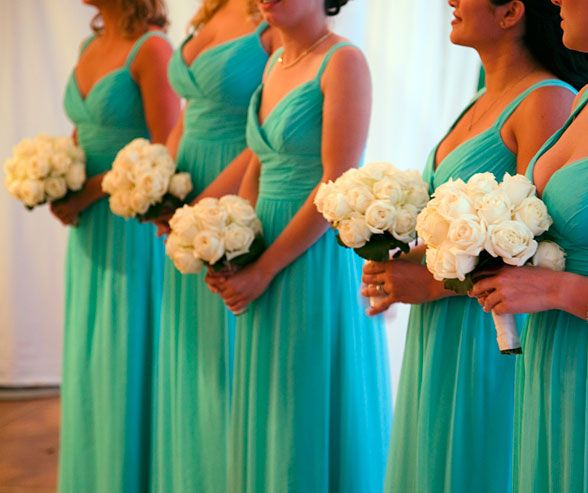 Bouquets of white roses wrapped with white satin ribbon look elegant against turquoise bridesmaids gowns.