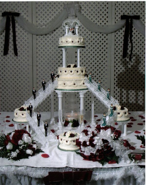 This is a two teir cake with three sattelite cakes.  A lighted fountain resides under the first teir, giving it an elegant touch.  All icing on the cake is buttercream icing, including the roses atop each layer.  The wedding colors were burgundy and hunter green.