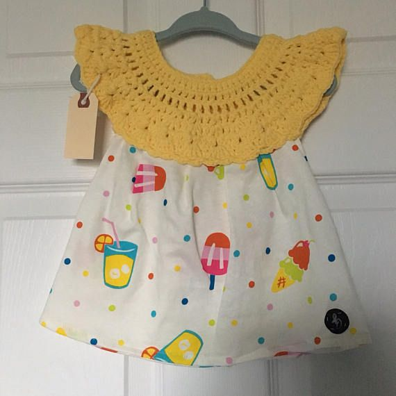 6-12 month size handmade baby girl dress with crochet top in pink cotton/nylon/polyester blend yarn with popsicle pattern cotton fabric skirt, fastened at the back with a button. Lightweight and pulls over the head.